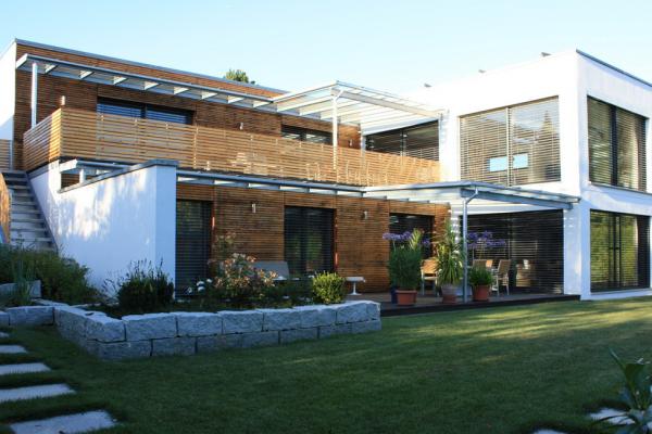 Das Bild zeigt die Rückansicht eines sanierten Mehrgenerationenhauses mit in Holz verkleideter Fassade / Quelle: Zukunft Altbau / Sanierungsgalerie